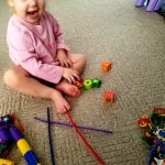 Toddler stacking blocks as a fine motor activity instead of threading the beads