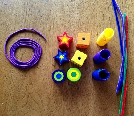 Large beads, strings, pipe cleaners for fine motor skill activities