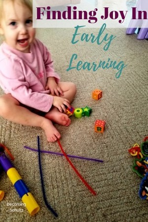 Finding joy in early learning, a toddler playing with big beads and pipe cleaners